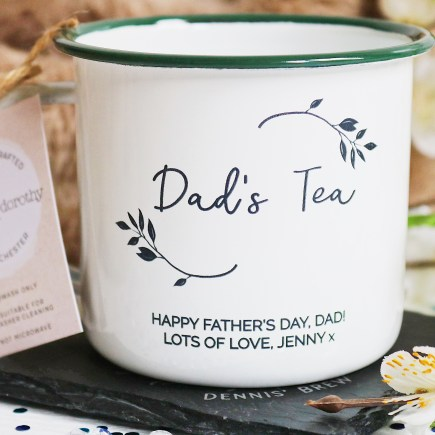 """Father's Day Gift Guide: Close up photo of a tin mug with Dad's Tea written on it, surrounded by flowers. The inscription """"Happy Father's Day Dad, Lots of Love, Jenny"""" is written on the bottom of the mug"""