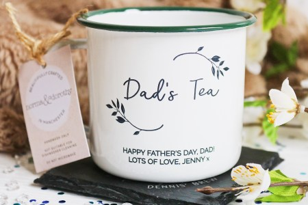 "Father's Day Gift Guide: Close up photo of a tin mug with Dad's Tea written on it, surrounded by flowers. The inscription ""Happy Father's Day Dad, Lots of Love, Jenny"" is written on the bottom of the mug"