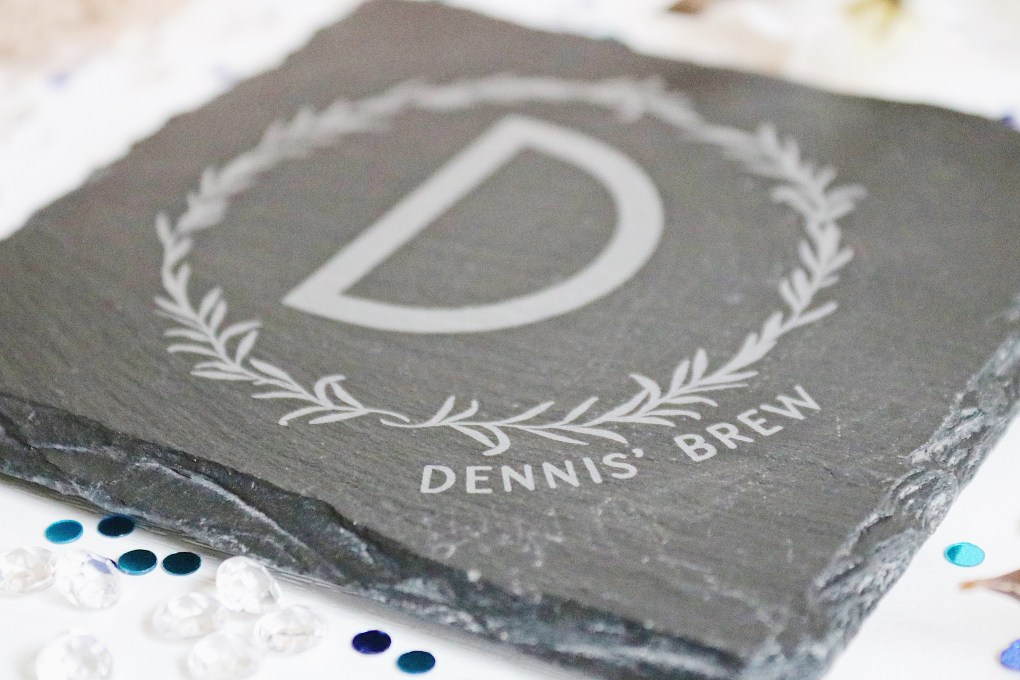 "Father's Day Gift Guide: Close up image of a dark grey slate mug coaster with the letter D surrounded by a leaf garland with ""Dennis' Brew"" written in the bottom right corner"