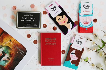 Unique Gift Ideas: Flat lay image of socks, a book and a poster