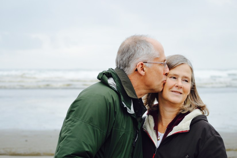Couple standing together on a beach kissing cheek