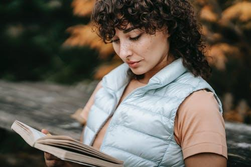 A person with curly hair, wearing a blue vest and salmon short-sleeved shirt, sits on a bench and reads a book.