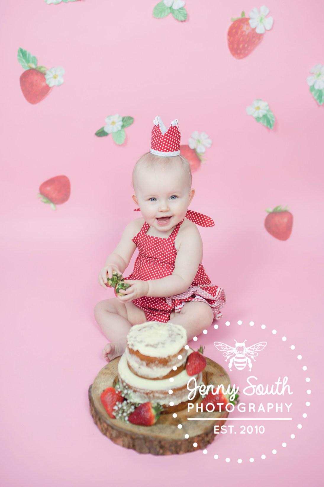 Baby girl enjoying her strawberry themed cake smash