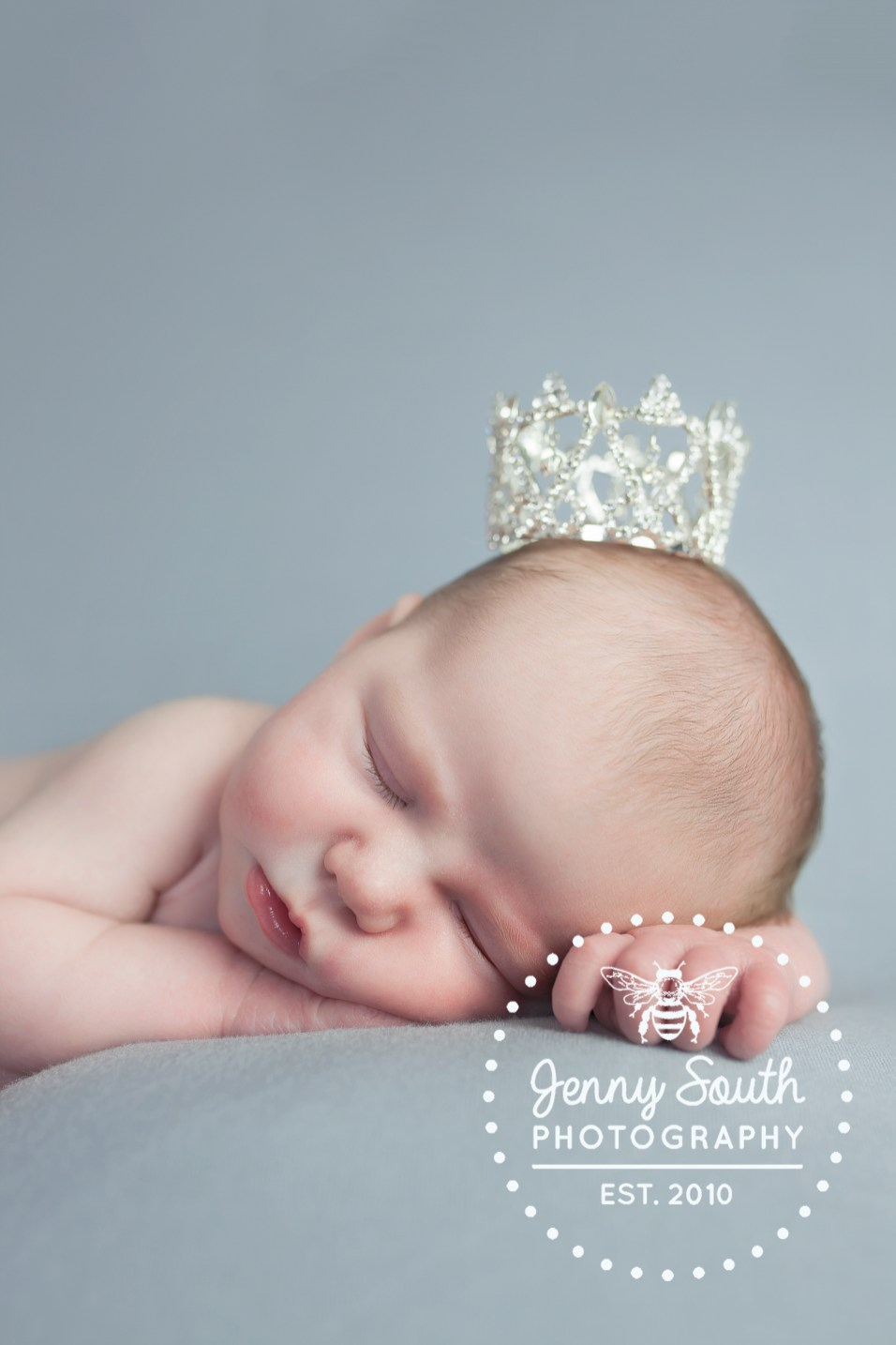 Sleeping newborn baby girl in tiny tiara