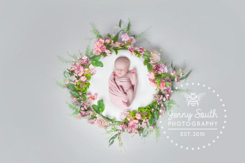 Newborn baby girl in floral spring wreath