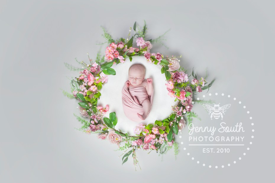 Newborn baby girl in floral spring wreath
