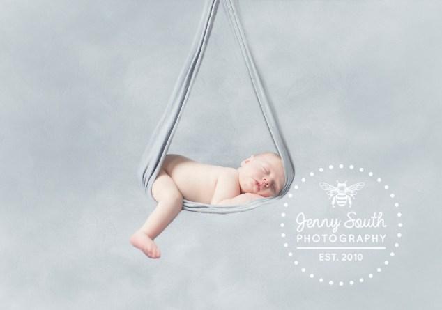 Newborn baby in a grey hammock