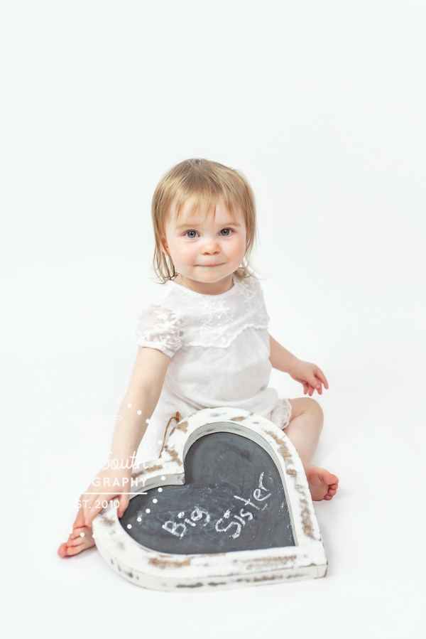 Big Sister to be wears white dress and holds chalk board saying big sister.