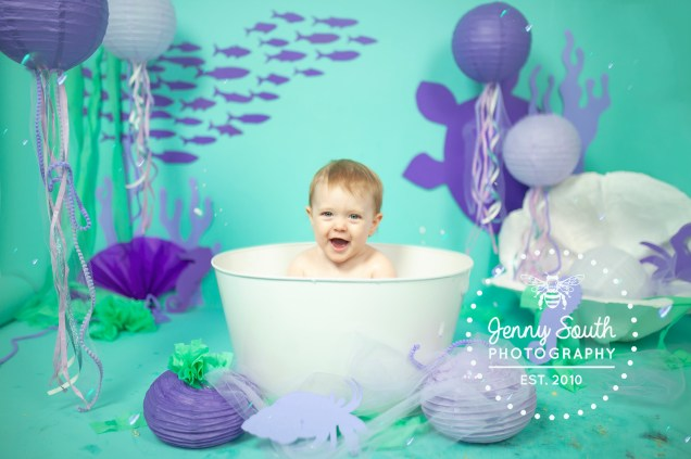 Baby girl in a bath tub surrounded by decoration of sea creatures for an underwater cake smash theme