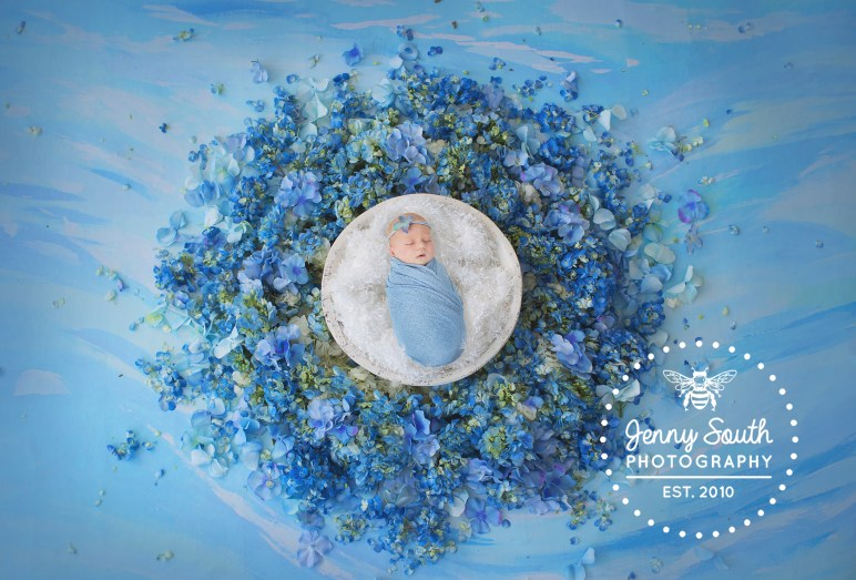 Baby girl sleeps amongst hydrangea petals onto of a waterscape handprinted backdrop