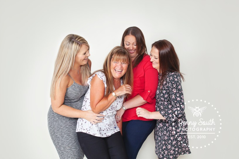 3 daughters tickle and laugh with their mother during a family session at our Plymouth Studio