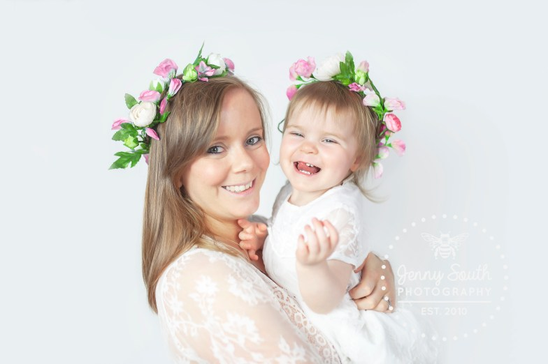 Mother and daughter picture wearing matching flower crowns and white dresses