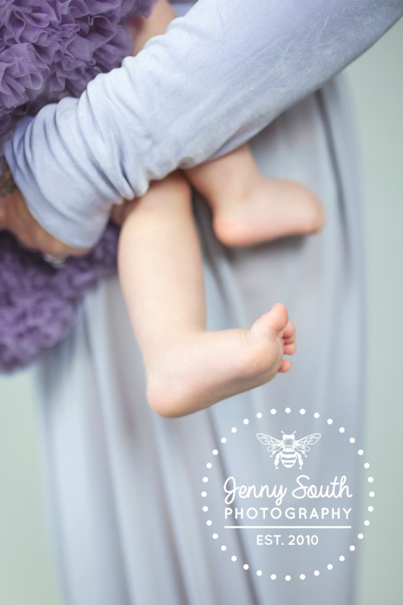 Mother and daughter wearing matching purple dress during a breastfeeding photoshoot in Plymouth
