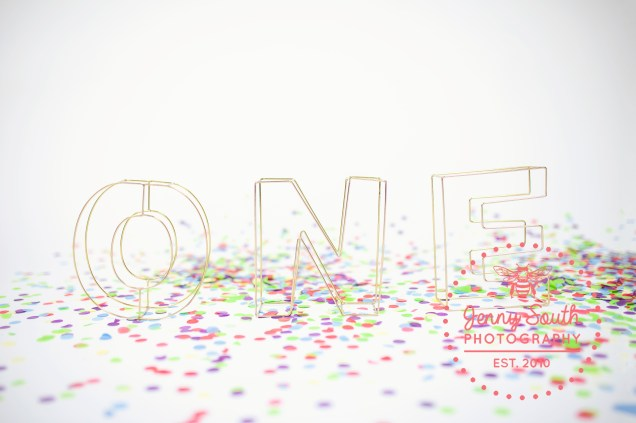 Gold wire letter spelling out the word one surrounded by confetti at the Jenny South Photography Studio
