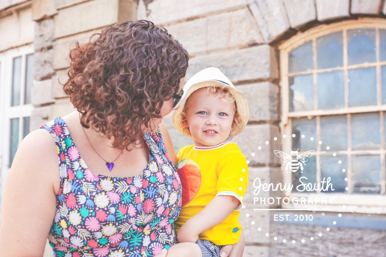A little boy excitedly smiles at the though of having an ice cream with his parents in the Royal William Yard