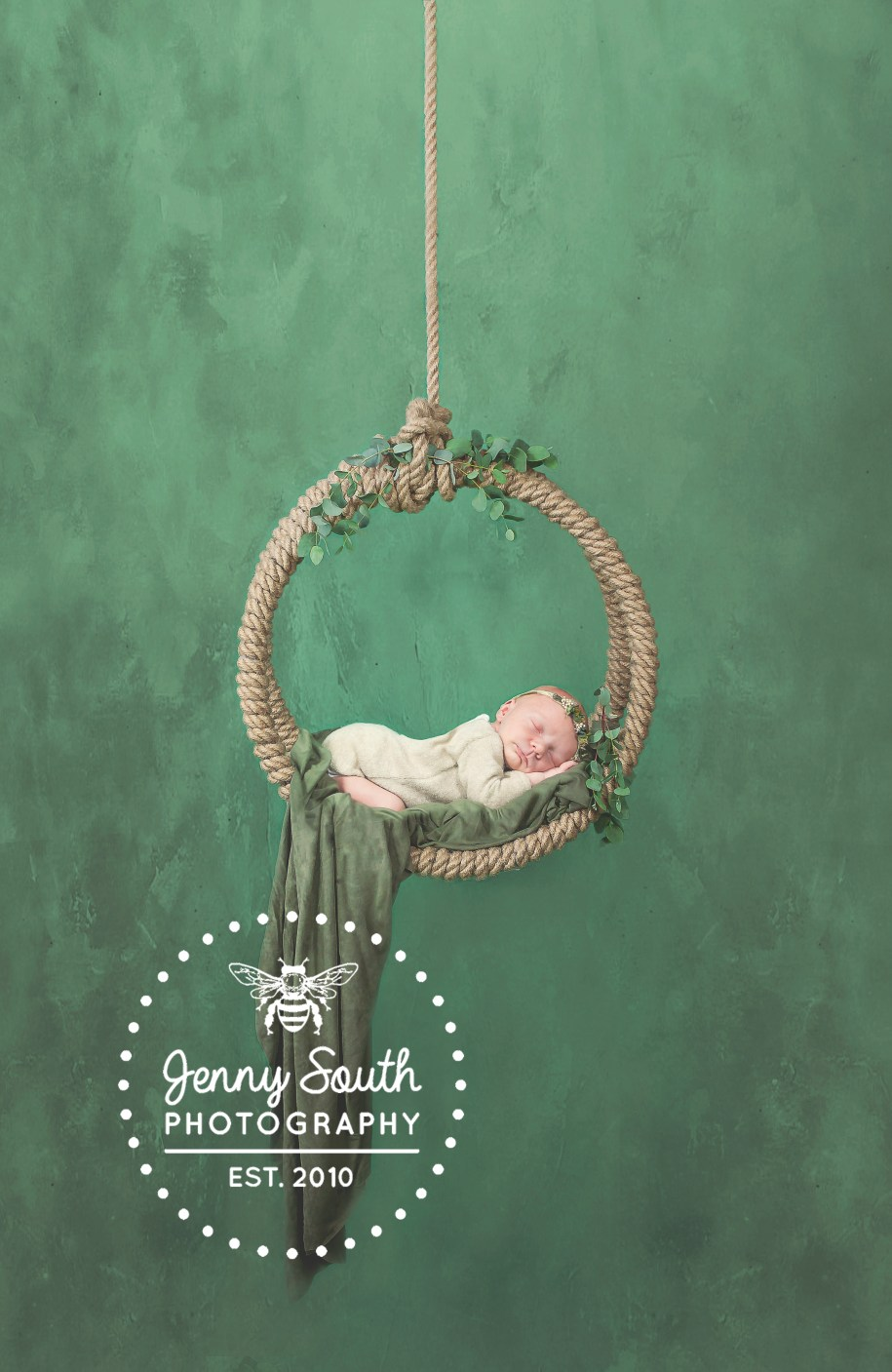 A rustic rope swing adorned with Eucalyptus leaves against a green fine art background. In it sleeps a newborn baby girl during her first photo shoot