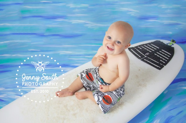 Baby sits on his fathers surfboard with Jenny South's hand painted waterscape backdrop.