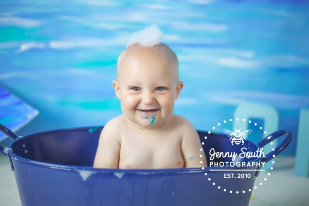 Baby boy chuckles in blue tin bath with bubbles on his head.