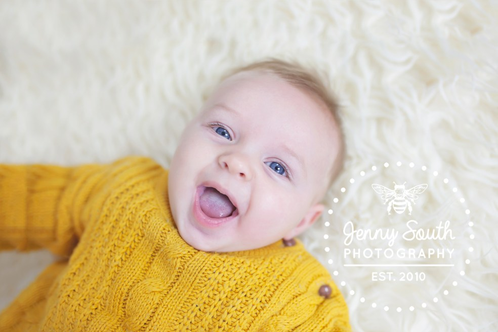 Baby boy grins with delight wearing a chunky knit mustard coloured jumper. laying on top of a cream fur