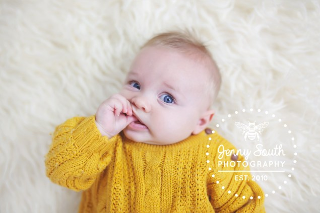 Baby boy chews on his finger wearing a chunky knit mustard coloured jumper. laying on top of a cream fur