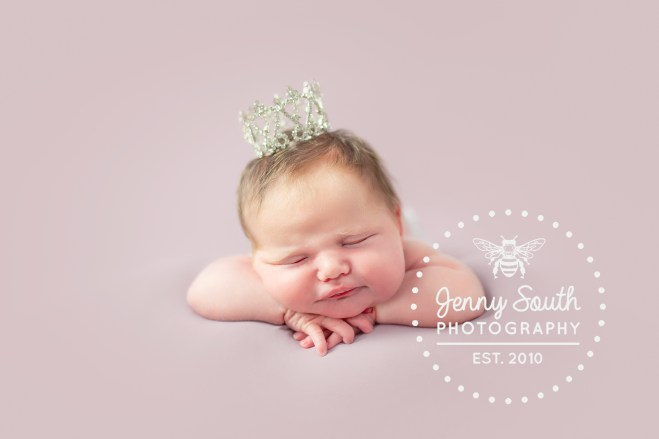 Newborn baby sleeps on her hands and tummy whist wearing a tiny crown.