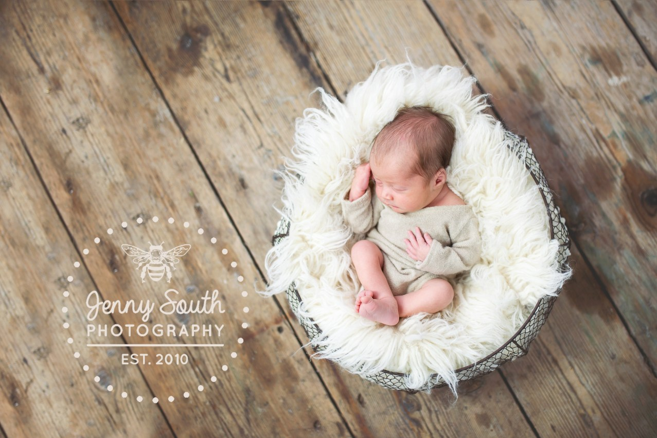 A newborn baby girl sleep soundly in a rustic wire basket stuffed with a white fur blanket
