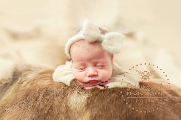 Baby girl sleeps soundly upon reindeer pelt in a stunning newborn photo