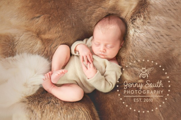 A baby girl sleeps all bundled up in a reindeer fur brought back from her fathers travels.