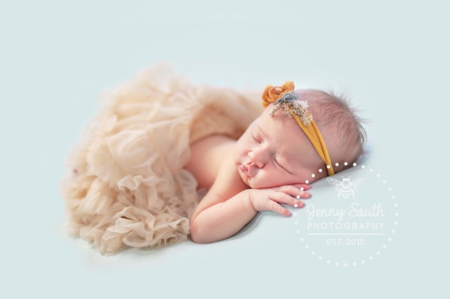 Baby girl sleeps whilst wearing a tutu against a blue backdrop.
