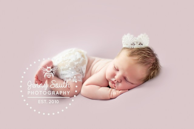 newborn baby girl sleeps on a lilac backdrop during her first photo shoot