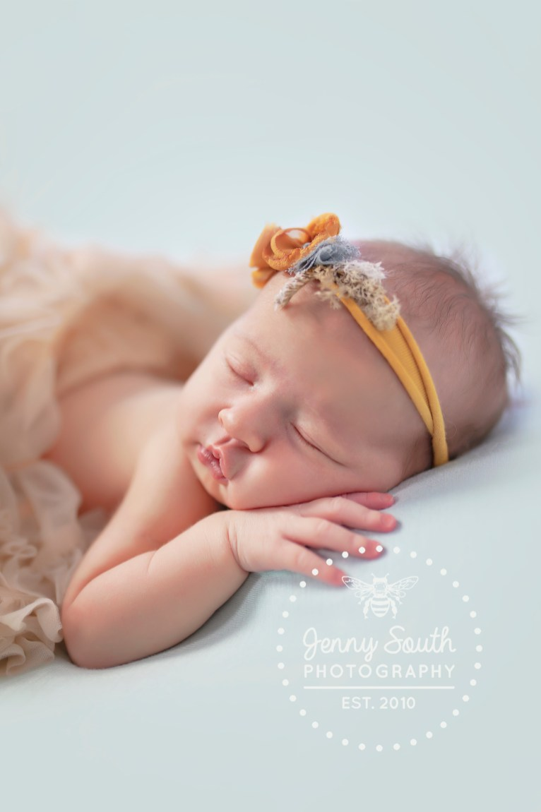 Newborn baby girl wears tulle tutu and flower tie back against a turquoise backdrop