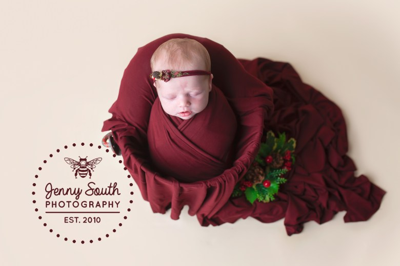 A baby girl sleeps in a bucket on top of a crimson blanket with a little nod to Christmas with some seasonal springs of holly.