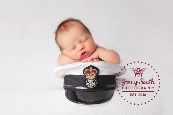 A baby girl sleeps soundly on top of her Daddy's military cap.