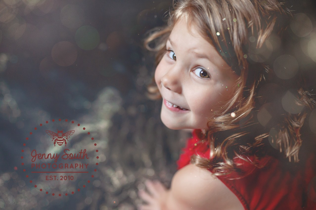 A Little girl smiles cheekily whilst making a mess with gold glitter.
