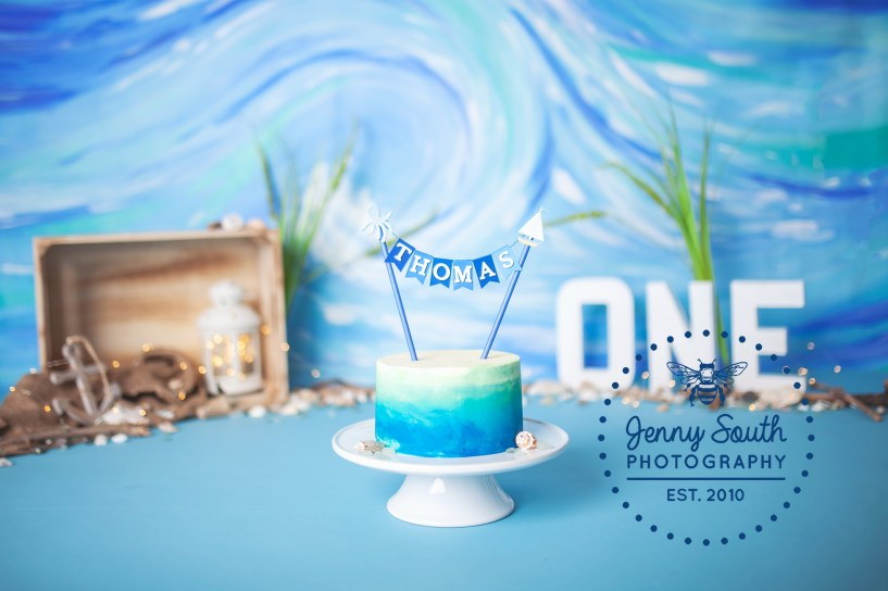 A first birthday cake sits amongst a beach themed set for a little boys birthday cake smash
