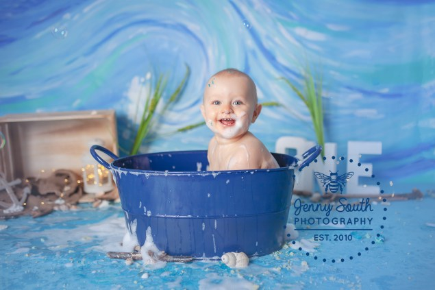 A baby sits in a blue tin tub, splashing water and bubbles every where around his beach themed set.