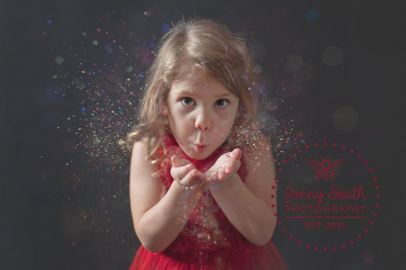 A little girl blows glitter at a camera during a glitter photo session at Jenny South Photography