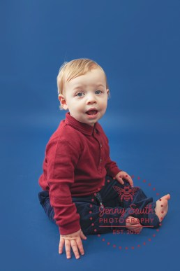 Baby boy sits against a navy backdrop during a portrait session.