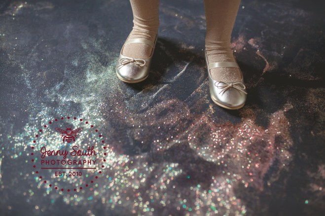 A little girl wears gold ballet shoes standing in a pile of glitter.