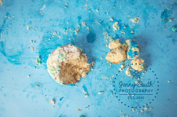 A cake lies smashed to pieces against an aqua backdrop.