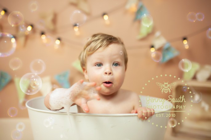A little boy coo's with delight at bubbles floating all around him.