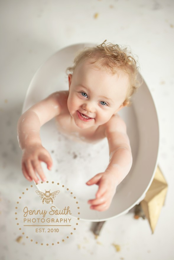 A little girl splashed with delight in a metal bath tub during a photo shoot in plymouth