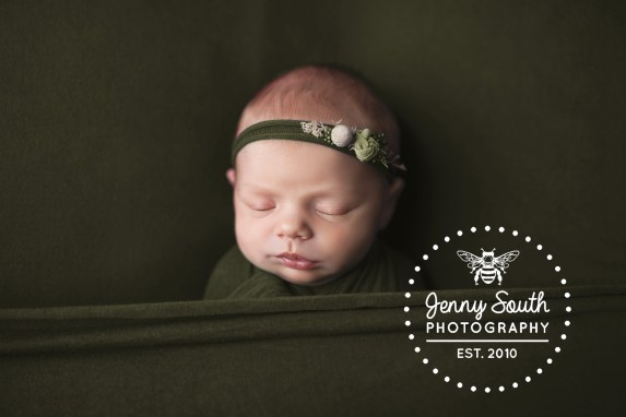 Baby girl lies sleeping soundly on a green backdrop in a matching wrap and headband