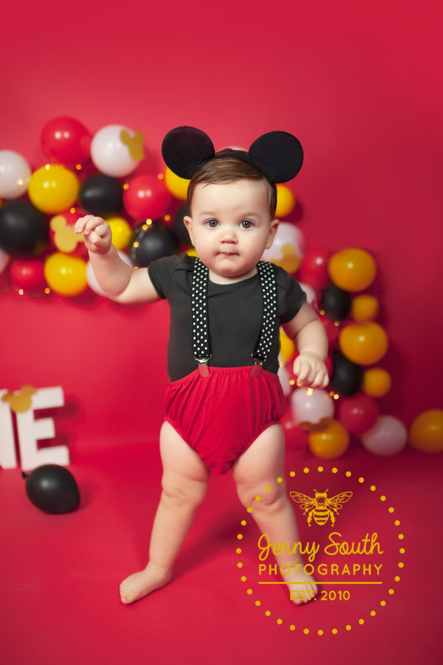 A little boy takes his first steps on a Mickey mouse themed photo shoot.