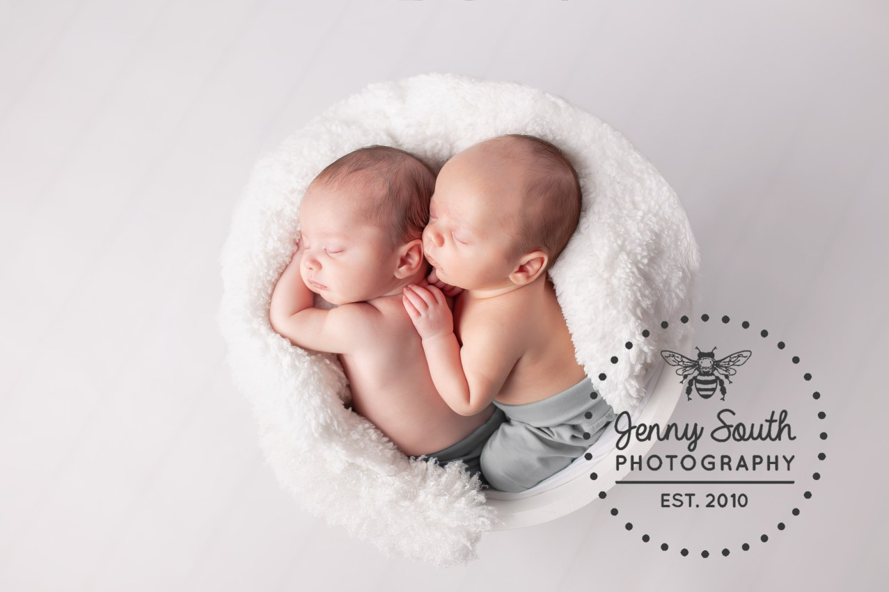 Twin brother cuddle each other in a white bucket during a twin newborn session