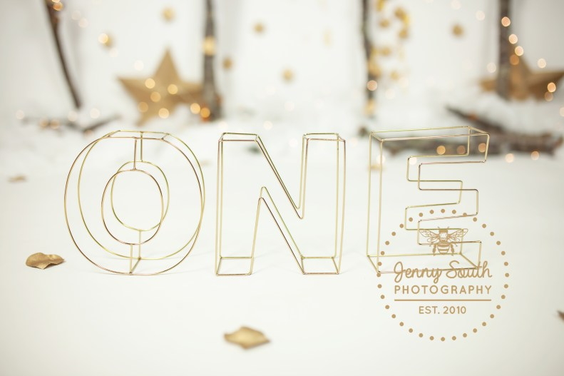 Gold letters spelling one look perfect on the festive forest background created for a Christmas cake smash