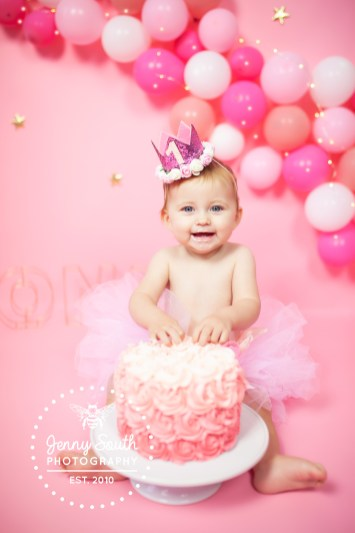 A little girl tuck into her pink fondant iced birthday cake during her cake smash photo shoot.
