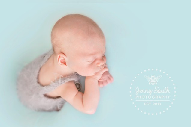 Newborn baby boy sleep on his hands in a mohair dungaree's outfit against a mint background