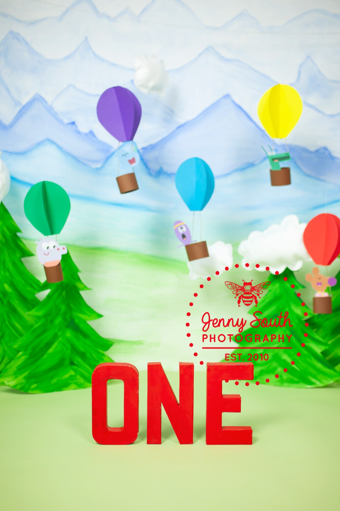 Letters that spell out the word one are painted a bright red and set against a hey Duggee adventure theme backdrop of mountains and hot air balloons.