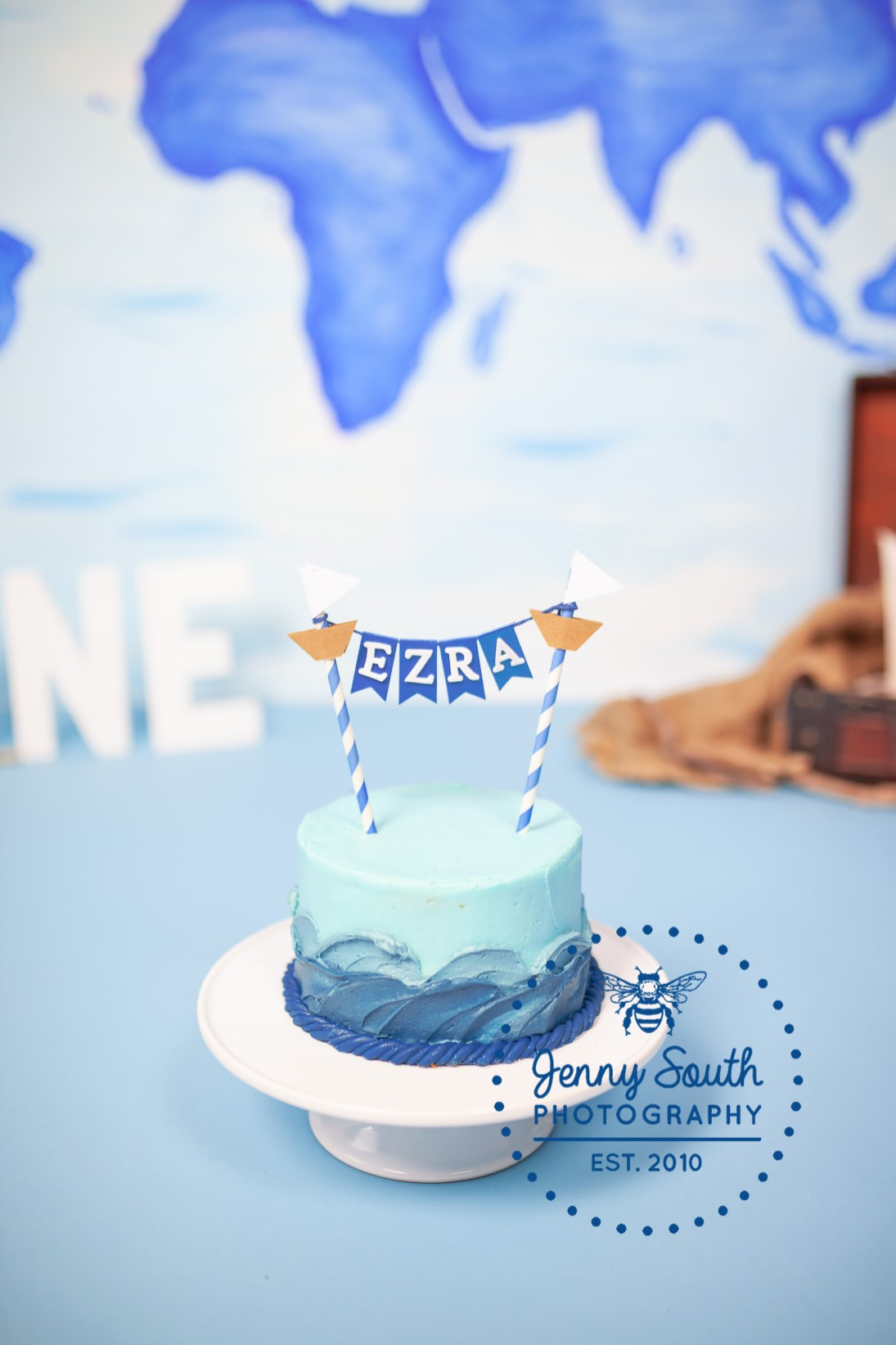 A nautical cake in shades of blue with a boat themed cake topper against a hand painted backdrop.